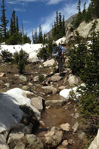 Trail wet from snow melt as it is  heading toward Pear Lake