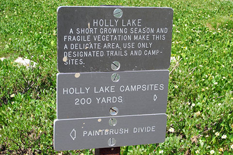 Holly Lake signs for minimum impact use, campsite direction, and the divide