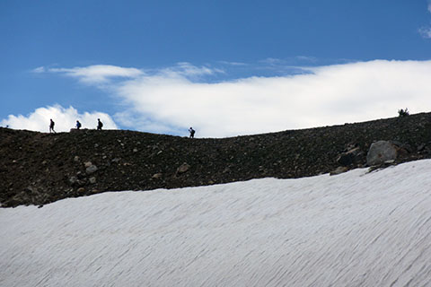 HIkers above snowfield on the Paintbrush Divide