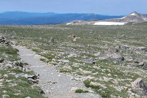 Hiker seen in the distance at the end of a trail. Hiker is wearing an orange jacket