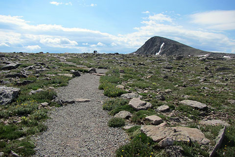 Trail aiming toward Hallett Peak standing over Flattop Mountain