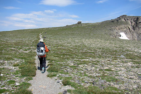 Hiker climbing towar Ptarmigan Point as the trail crosses alpine tundra
