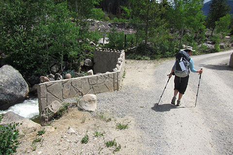 HIker crossing a bridge over Tonahutu Creek on gravel Road 633.