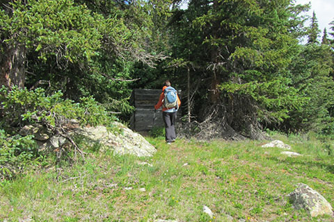 a short walled privy sitting close to the trail